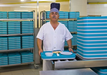 Chef stands in hospital kitchen with plastic trays