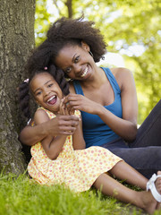 African mother and daughter hugging in park