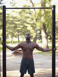 African man standing below fitness bar in park