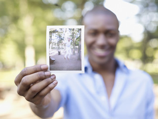 African man holding photograph