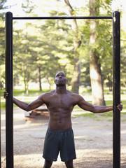African man standing below fitness bar in park