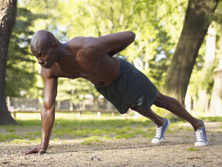 African man doing one arm push-ups in park