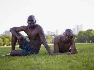 African men laying in grass at park