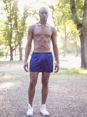Serious African man standing in park with bare chest