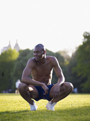 African man crouching in park