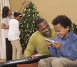 Father and son playing hand-held video game while mother and daughter decorate Christmas tree