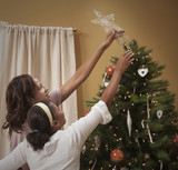 Mother and daughter placing star on Christmas tree