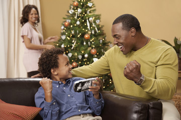 Father and son playing hand-held video game while mother decorates Christmas tree