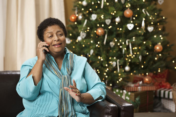 African woman talking on cell phone with Christmas tree in background