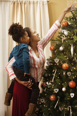 Mother holding daughter and placing star on Christmas tree
