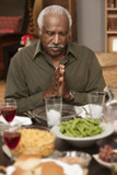 African man saying grace at dinner table