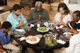 Multi-generation family saying grace at dinner table