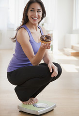 Hispanic woman holding donut and crouching on scale