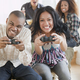 Man and woman playing video game and making faces