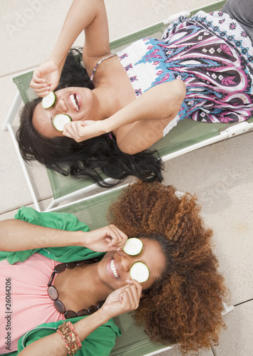 Women laying on lounge chairs with cucumbers over eyes