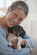 Chinese woman holding dachshund