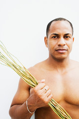 Mixed race man with bare chest holding sticks