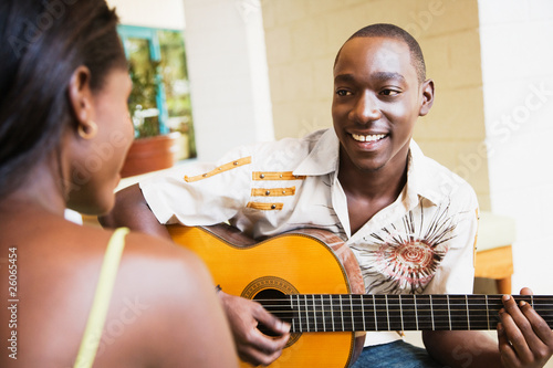 African man playing guitar for woman