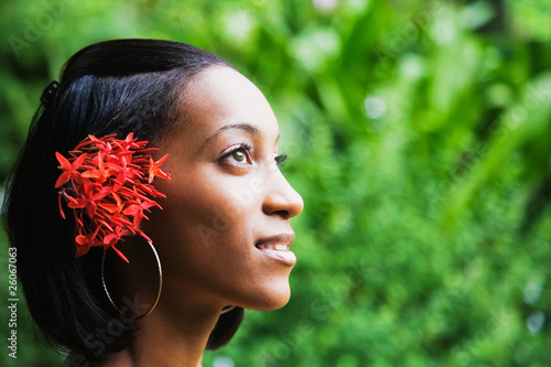African woman with flowers in hair looking up