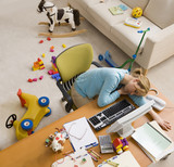 Hispanic woman sleeping at desk surrounded by toys