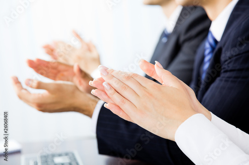 Close up clapping hands of businesspeople at presentation