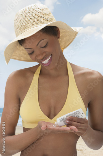 African woman applying sunscreen on beach