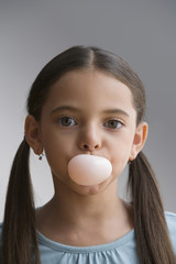 Hispanic girl blowing bubble