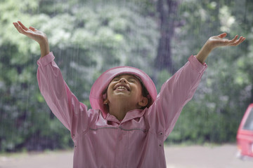 Hispanic girl standing in rain with arms raised