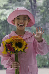 Hispanic girl holding flowers in rain and waving