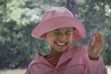 Hispanic girl standing in rain with eyes closed