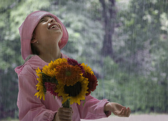 Hispanic girl holding flowers in rain