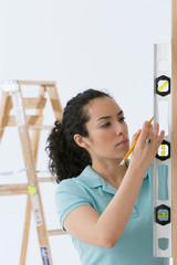 Hispanic woman using spirit level tool