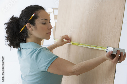 Hispanic woman measuring wood board