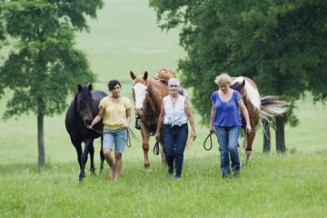 Multi-generation Hispanic women walking horses in field