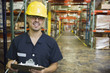 Hispanic man holding clipboard in warehouse