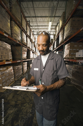 African man completing paperwork in warehouse