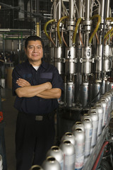 Hispanic man with arms crossed in manufacturing plant