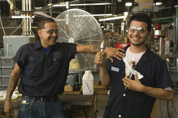 Hispanic men smiling in manufacturing plant