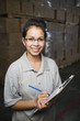 Hispanic woman with clipboard smiling in warehouse