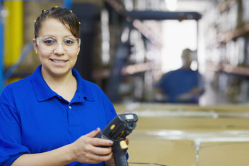 Hispanic woman holding tracking device in warehouse