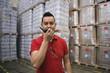 Hispanic man using walkie-talkie in warehouse