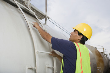 Hispanic man climbing tanker truck