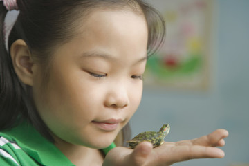 Chinese girl holding miniature turtle