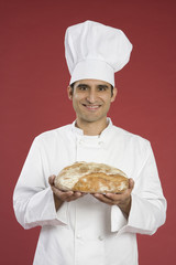 Hispanic chef holding fresh baked bread