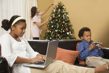 Boy and girl using technology devices while mother decorates Christmas tree