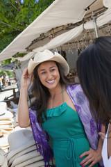 Smiling Hispanic woman trying on cowboy hat