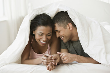 Couple holding hands and laying under blanket in bed
