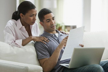 Couple with laptop and paperwork in living room