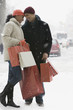 Couple holding shopping bags in snow