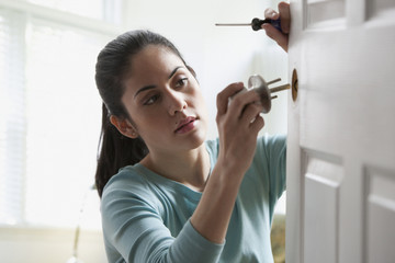 Mixed race woman fixing doorknob